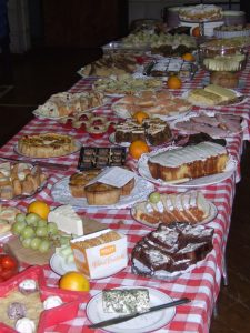 A Table laden with sweet cakes and biscuits and cheese